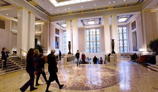 FILE - In this Oct. 6, 2014 file photo, guests pass through Park Avenue lobby of the Waldorf Astoria hotel decorated with an immense floor mosaic by the French artist Louis Rigal, in New York. New York City has landmarked historic interiors throughout the Waldorf Astoria to preserve them as the hotel's Chinese owners start a yearslong renovation. The Landmarks Preservation Commission voted Tuesday, March 7, 2017, to keep the Art Deco details in dozens of spaces in the grand Park Avenue building. (AP Photo/Mark Lennihan, FIle)
