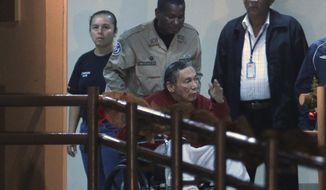 In this Dec. 11, 2011, file photo, Panama's ex-dictator Manuel Noriega is pushed in a wheelchair by a police officer inside El Renacer prison on the outskirts of Panama City. Noriega, 83, is in critical condition after undergoing two brain surgeries Tuesday, March 7, 2017. Noriega underwent the first procedure Tuesday morning to remove a benign tumor from his brain. But after that surgery, doctors discovered a hemorrhage that forced them to go back in that afternoon, his daughters and lawyer said. (AP Photo/Esteban Felix, File)