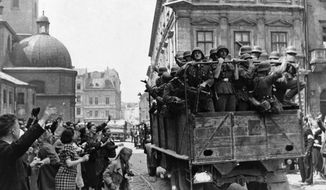 Inhabitants of Lwow  on July 2, 1941, Soviet occupied former Poland wave at a passing truckload of German solders as Nazi troops took over the city. (AP Photo) ** FILE **