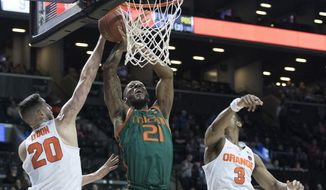 Miami forward Kamari Murphy (21) goes to the basket past Syracuse forward Tyler Lydon (20) and guard Andrew White III (3) during the first half of an NCAA college basketball game in the Atlantic Coast Conference tournament, Wednesday, March 8, 2017, in New York. (AP Photo/Mary Altaffer)