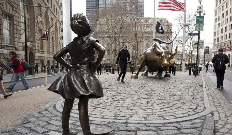 "A statue titled ""Fearless Girl"" faces the Wall Street bull, Wednesday, March 8, 2017, in New York.   A big investment firm, State Street Global Advisors, put the statue there to highlight International Women's Day.  The work by artist Kristen Visbal.  (AP Photo/Mark Lennihan)"