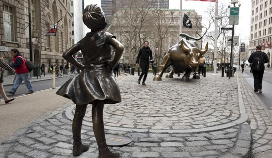 """A statue titled """"Fearless Girl"""" faces the Wall Street bull, Wednesday, March 8, 2017, in New York.   A big investment firm, State Street Global Advisors, put the statue there to highlight International Women's Day.  The work by artist Kristen Visbal.  (AP Photo/Mark Lennihan)"""