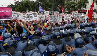 Police block women during a rally at the U.S. Embassy to mark International Women's Day Wednesday, March 8, 2017 in Manila, Philippines. Women all over the world mark the women's day with rallies and protests to highlight the role of women in society. (AP Photo/Bullit Marquez)