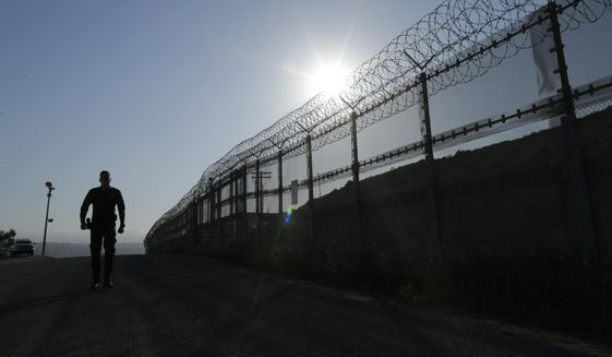 In this June 22, 2016, file photo, a Border Patrol agent walks along a border structure in San Diego, Calif. (AP Photo/Gregory Bull, file)
