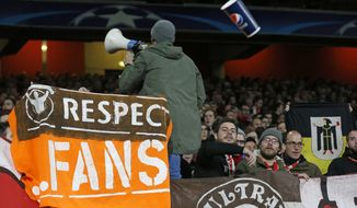 A Bayern supporter throws a paper cup during the Champions League round of 16 second leg soccer match between Arsenal and Bayern Munich at the Emirates Stadium in London, Tuesday, March 7, 2017. (AP Photo/Frank Augstein)