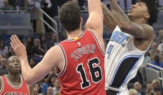 Orlando Magic guard Elfrid Payton (4) goes up for a shot in front of Chicago Bulls forward Paul Zipser (16) and guard Jerian Grant (2) during the first half of an NBA basketball game in Orlando, Fla., Wednesday, March 8, 2017. (AP Photo/Phelan M. Ebenhack)