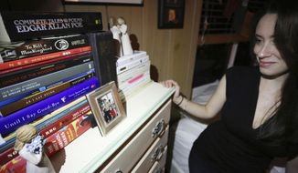 In this Feb. 13, 2017 photo, Casey Anthony poses next to a photo of her daughter Caylee during an interview in her West Palm Beach, Fla., home. Anthony, 30, opens up for the first time on-the-record about the death of her daughter in 2008. (AP Photo/Joshua Replogle)