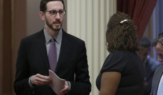 FILE - In this Jan. 26, 2017 file photo, state Sen. Scott Wiener, D-San Francisco, left, talks with Sen. Holly Mitchell, D-Los Angeles, at the Capitol, in Sacramento, Calif. At a news conference, Wednesday, March 8, 2017, Wiener discussed his bill to make it a misdemeanor instead of a felony to intentionally expose someone to HIV. If approved by the Legislature and signed by the governor, Wiener's bill would repeal laws passed at the height of the AID's epidemic that he says unfairly punishes HIV-positive people based on outdated science. (AP Photo/Rich Pedroncelli,file)