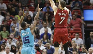 Miami Heat guard Goran Dragic (7) shoots as Charlotte Hornets guard Kemba Walker (15) defends during the first half of an NBA basketball game, Wednesday, March 8, 2017, in Miami. (AP Photo/Alan Diaz)
