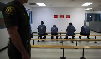 FILE--In this Sept. 28, 2010, file photo, an Orange County Sheriff's deputy keeps a watch over a group of immigration detainees in the medical and dental care area at the Theo Lacy Facility in Orange, Calif. The Department of Homeland Security's Inspector General on Wednesday, Mar. 8, 2017, reported health risks and safety concerns at the Theo Lacy Facility. (AP Photo/Jae C. Hong, file)