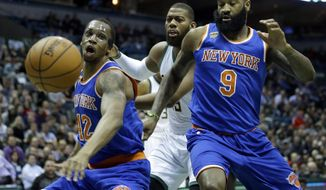New York Knicks' Lance Thomas (42), Kyle O'Quinn (9), and Milwaukee Bucks' Greg Monroe, middle, watch as the ball bounces out of bounds during the first half of an NBA basketball game, Wednesday, March 8, 2017, in Milwaukee. (AP Photo/Aaron Gash)
