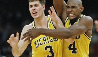 FILE - In this April 3, 1993 file photo, Michigan's Chris Webber (4) and Rob Pelinka (3) celebrate in New Orleans as they defeated Kentucky 81-78 in overtime to advance to the NCAA college basketball championship game against North Carolina. Longtime sports agent Rob Pelinka, whose clients included Kobe Bryant, was formally named the Los Angeles Lakers' new general manager Tuesday, March 7, 2017. (AP Photo/Ed Reinke, File)