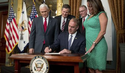 FILE - In this March 1, 2017 file photo, Vice President Mike Pence, left, Sen. Steve Daines, R-Mont., second from left, Montana Attorney General Tim Fox, second from right, and Lolita Hand, right, watches as Interior Secretary Ryan Zinke signs an official document in the Eisenhower Executive Office Building on the White House complex in Washington. Lolita Hand is Zinke's wife. Zinke was the Republican Party's first choice to take on incumbent Democratic Sen. Jon Tester in 2018, but President Donald Trump dashed those hopes by snatching the former congressman to become his interior secretary. Now the Republicans in Montana and in Washington, D.C., are now courting Fox to step up and run against Tester. (AP Photo/Andrew Harnik, File)