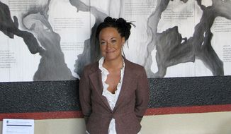 FILE - In this July 24, 2009, file photo, Rachel Dolezal, a leader of the Human Rights Education Institute, stands in front of a mural she painted at the institute's offices in Coeur d'Alene, Idaho. Court documents show Dolezal legally changed her name to Nkechi Amare Diallo on Oct. 7, 2016.(AP Photo/Nicholas K. Geranios, File)