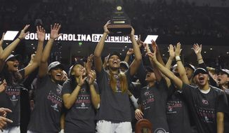 South Carolina forward A'ja Wilson (22) holds the trophy as she celebrates with teammates after defeating Mississippi State in an NCAA college basketball game during the Southeastern Conference tournament on Sunday, March 5, 2017, in Greenville, S.C. Wilson was named the tournament MVP. (AP Photo/Rainier Ehrhardt)