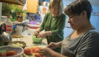 In this Tuesday, Feb. 28, 2017 photo, Ruth Silverberg, left, helps Maribel Torres prepare dinner at Maribel's home in the Staten Island borough of New York. Silverberg is one of about 30 local residents meeting regularly with Latino neighbors who lack legal status, to study ways to help them. Torres and Silverberg and their sons had dinner together to get to know each other and practice English and Spanish. (AP Photo/Mary Altaffer)