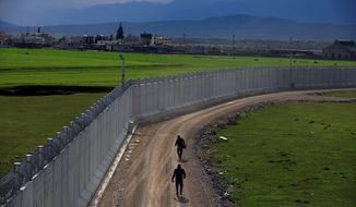A Turkish army officer patrols a wall under construction near Kilis to help boost security along the border with conflict-stricken Syria. (Associated Press)