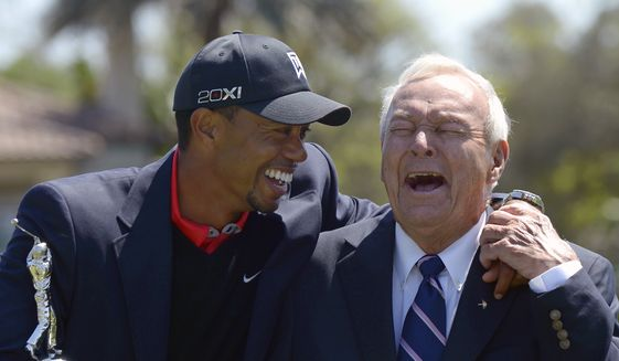 FILE - In this Monday, March 25, 2013 file photo, Tiger Woods, left, and Arnold Palmer share a laugh during the trophy presentation after Woods won the Arnold Palmer Invitational golf tournament in Orlando, Fla. Tiger Woods won't be at the Arnold Palmer Invitational next week and still doesn't know when he will play again. Woods announced on his website Thursday night, March 9, 2017 that ongoing rest and rehabilitation on his back will keep him away from Bay Hill and the tournament he has won a record eight times. (AP Photo/Phelan M. Ebenhack, File) **FILE**