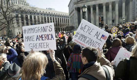 People hold anti-deportation signs during a rally, Thursday, March 9, 2017, in New York. The rally was held in support of Ravi Ragbir, leader of the New Sanctuary Coalition, and an immigrant from Trinidad, who may face deportation. (AP Photo/Mark Lennihan)