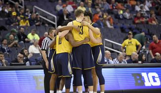 Michigan forward Moritz Wagner (13) and others huddle up before an NCAA college basketball game in the Big Ten tournament against Illinois, Thursday, March 9, 2017, in Washington. The team's flight to Washington was aborted on Wednesday because of airplane trouble, then rescheduled for Thursday morning. After dealing with the travel trouble, Michigan's players wore practice jerseys instead of normal game uniforms to face Illinois. (AP Photo/Nick Wass)