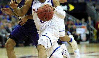 Kansas guard Frank Mason III (0) drives on TCU guard Alex Robinson, left, during first half of an NCAA college basketball game in the quarterfinal round of the Big 12 tournament in Kansas City, Mo., Thursday, March 9, 2017. (AP Photo/Orlin Wagner)