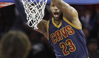Cleveland Cavaliers forward LeBron James points after dunking during the first half of the team's NBA basketball game against the Detroit Pistons, Thursday, March 9, 2017, in Auburn Hills, Mich. (AP Photo/Carlos Osorio)