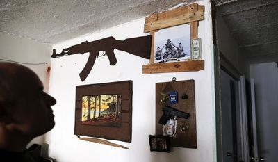 In this Feb. 13, 2017 photo, U.S. Marine veteran Antonio Romo looks at a replica of a pistol and other military items from his time in the service, mounted on his apartment wall in Tijuana, Mexico. Romo, who says he turned to alcohol and narcotics to try to quiet his nightmares and made multiple suicide attempts, fell into dealing and was arrested for selling cocaine. After getting out of prison in 2008, Romo was deported to Mexico, from where he had migrated without permission at age 12. (AP Photo/Gregory Bull)
