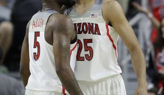 Arizona's Kadeem Allen, left, and Keanu Pinder celebrate after a play against Colorado during the first half of an NCAA college basketball game in the quarterfinals of the Pac-12 men's tournament Thursday, March 9, 2017, in Las Vegas. (AP Photo/John Locher)