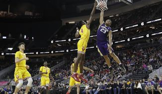 Washington's Carlos Johnson, right, attempts a dunk over Southern California's Chimezie Metu during the first half of an NCAA college basketball game in the first round of the Pac-12 men's tournament Wednesday, March 8, 2017, in Las Vegas. (AP Photo/John Locher)