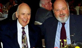 FILE - In this Aug. 18, 2000 file photo, Carl Reiner, left, appears with his son Rob Reiner at a Friars Club of California dinner in his honor in Beverly Hills, Calif. The Reiners are set to make history at the TCL Chinese Theatre, becoming the first father and son to jointly leave their cement footprints outside the Hollywood landmark on April 7, 2017.  (AP Photo/Reed Saxon, File)