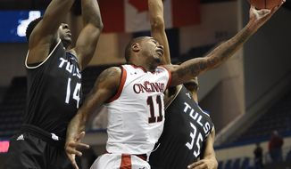 Cincinnati's Gary Clark, center, is fouled by Tulsa's Geno Artison, right, as Tulsa's TK Edogi, left, defends, during the first half of an NCAA college basketball game in the American Athletic Conference tournament quarterfinals, Friday, March 10, 2017, in Hartford, Conn. (AP Photo/Jessica Hill)
