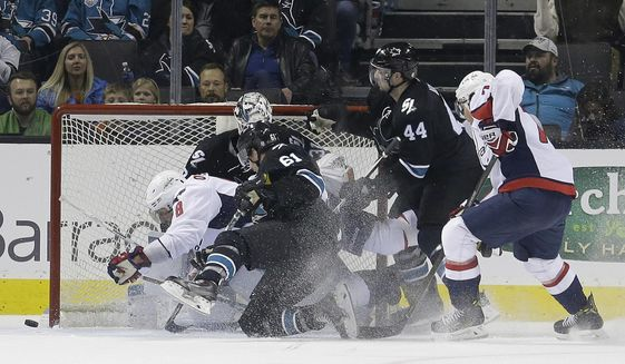 Washington Capitals left wing Alex Ovechkin (8) crashes into San Jose Sharks goalie Martin Jones, rear, and defenseman Justin Braun (61) during the second period of an NHL hockey game in San Jose, Calif., Thursday, March 9, 2017. (AP Photo/Jeff Chiu)