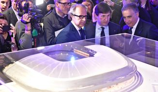 Fiorentina's owner Diego Della Valle, left, Florence's mayor Diego Nardella, center, and Fiorentina's executive president Mario Cognini, right, look at a plastic model of the new stadium in Florence, Italy, Friday, March 10, 2017. Fiorentina has unveiled plans for a new stadium on Friday, which it hopes to be playing in by 2021. The new stadium will seat 40,000 people, with the closest fans being only seven meters from the field. (Maurizio Degl'Innocenti/ANSA via AP)