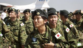 FILE - In this Nov. 21, 2016 file photo, members of the Japan Self-Defense Forces arrive as part of a first batch who have a broader mandate to use force at the airport in Juba as Japanese peacekeepers landed in South Sudan in the first such deployment of the country's troops overseas with those expanded powers in nearly 70 years. The Japanese government has decided to end its peacekeeping mission in South Sudan after five years. Prime Minister Shinzo Abe said Friday, March 10, 2017, that Japan will not renew the mission after the current rotation returns in May. The 350-person infrastructure team was focused on road construction. (AP Photo/Justin Lynch, File)