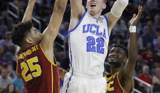 UCLA's TJ Leaf shoots over Southern California's Bennie Boatwright, left, and Chimezie Metu during the second half of an NCAA college basketball game in the quarterfinals of the Pac-12 men's tournament Thursday, March 9, 2017, in Las Vegas. (AP Photo/John Locher)