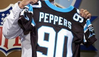 FILE - In this April 20, 2002, file photo, Julius Peppers, of North Carolina, holds up a team jersey after being selected by the Carolina Panthers as their first pick, second overall, in the NFL Draft in New York. After eight years, Peppers is returning home to play for the Panthers. The Panthers agreed to terms on a contract Friday, March 10, 2017, with Peppers, their all-time sack leader, according to a person familiar with the negotiations. The person spoke to The Associated Press on Friday on condition of anonymity because the move can't officially be announced until later in the day. (AP Photo/Ed Betz, File)