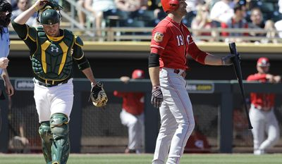 Oakland Athletics' Stephen Vogt walks to the dugout as Cincinnati Reds' Joey Votto reacts to striking out during the first inning of a spring training baseball game Thursday, March 9, 2017, in Mesa, Ariz. (AP Photo/Darron Cummings)