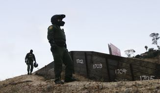 In this June 22, 2016 photo, Border Patrol agents stands near a border structure in San Diego. (AP Photo/Gregory Bull)