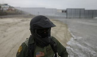 In this June 22, 2016, photo, a Border Patrol agent sits on a vehicle near where the border meets the Pacific Ocean in San Diego. (AP Photo/Gregory Bull)
