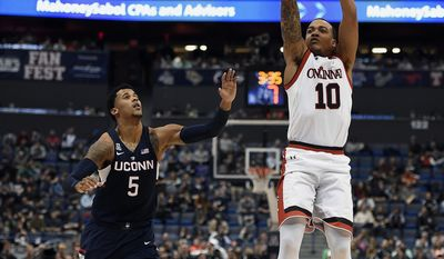 Cincinnati's Troy Caupain, right, shoots as Connecticut's Vance Jackson, left, looks on during the first half of an NCAA college basketball game in the American Athletic Conference tournament semifinals, Saturday, March 11, 2017, in Hartford, Conn. (AP Photo/Jessica Hill)