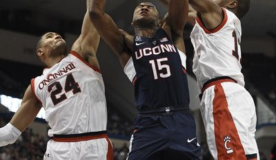 Cincinnati's Kyle Washington, left, fouls Connecticut's Rodney Purvis as Cincinnati's Gary Clark, right, defends, during the second half of an NCAA college basketball game in the American Athletic Conference tournament semifinals, Saturday, March 11, 2017, in Hartford, Conn. (AP Photo/Jessica Hill)