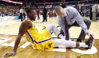 Minnesota guard Akeem Springs (0) is checked by a trainer after an injury during the second half of an NCAA college basketball game against Michigan State in the Big Ten tournament, Friday, March 10, 2017, in Washington. Springs did not return to the game. (AP Photo/Alex Brandon)