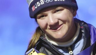 FILE - In this Feb. 10, 2002, file photo, Kelly Clark, of the U.S., gold medalist in the women's halfpipe snowboarding competition, holds up her medal at Medals Plaza in Salt Lake City. Clark, with her gold medal and two bronze that she values every bit as much,  has nothing left to prove, this is the road she was willing to travel to make sure she leaves the competitive side of her sport on her terms, not on anyone else's. The 33-year-old snowboarding icon is willing to try for a fifth trip to the Olympic halfpipe.  (AP Photo/Peter Dejong, File)