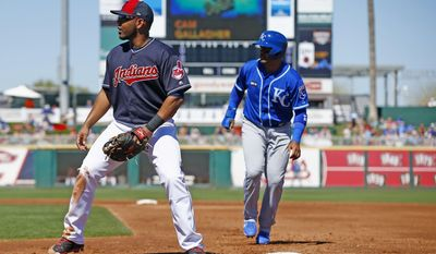 Cleveland Indians first baseman Edwin Encarnacion, left, looks for a possible pickoff throw from the catcher as Kansas City Royals' Christian Colon, right, runs back to first base during the second inning of a spring training baseball game Saturday, March 11, 2017, in Goodyear, Ariz. (AP Photo/Ross D. Franklin)