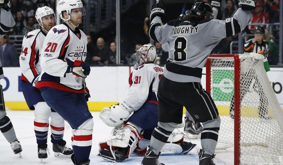 Los Angeles Kings defenseman Drew Doughty, right, celebrates next to Washington Capitals center Lars Eller, left, of Denmark, and goalie Philipp Grubauer, center, of Germany, after the Kings scored a goal during the second period of an NHL hockey game, Saturday, March 11, 2017, in Los Angeles. (AP Photo/Ryan Kang)