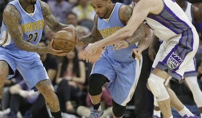 Denver Nuggets guard Jameer Nelson, center, runs between teammate Wilson Chandler, left, and Sacramento Kings center Kosta Koufos, right, to grab a loose ball during the first half of an NBA basketball game, Saturday, March 11, 2017, in Sacramento, Calif. (AP Photo/Rich Pedroncelli)