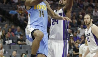 Denver Nuggets guard Gary Harris, left, drives to the basket against Sacramento Kings guard Buddy Hield during the first half of an NBA basketball game, Saturday, March 11, 2017, in Sacramento, Calif. (AP Photo/Rich Pedroncelli)