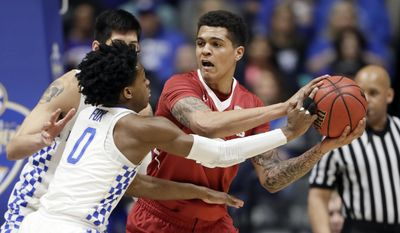 Arkansas forward Dustin Thomas is defended by Kentucky's De'Aaron Fox (0) in the first half of an NCAA college basketball game for the championship of the Southeastern Conference tournament Sunday, March 12, 2017, in Nashville, Tenn. (AP Photo/Wade Payne)
