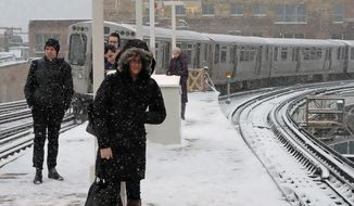 Commuters dealt with snowfall on Monday in Chicago, which had no accumulation in January and February for the first time in 146 years, according to the National Weather Service. The massive storm is disrupting travel in the Northeast. (Associated Press)