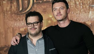 "FILE - In this Feb. 20, 2017, file photo, actor Josh Gad, left, who plays manservant LeFou and Luke Evans who plays villain Gaston, pose during a promotional event for the movie ""Beauty and the Beast"", in Paris. Walt Disney has shelved the release of its new movie ""Beauty and the Beast"" in mainly Muslim Malaysia, even though film censors said Tuesday, March 14, 2017, it had been approved with a minor cut involving a ""gay moment"" between two characters in the film. (AP Photo/Christophe Ena, File)"